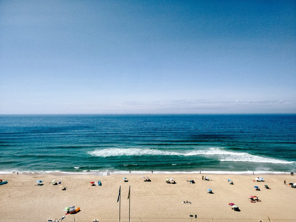 People sunbathing on a beach in Portugal.
