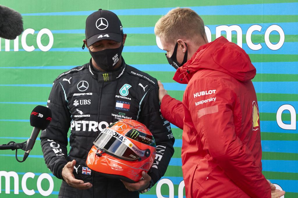 Lewis Hamilton is gifted Michael Schumacher's helmet by Mick Schumacher.