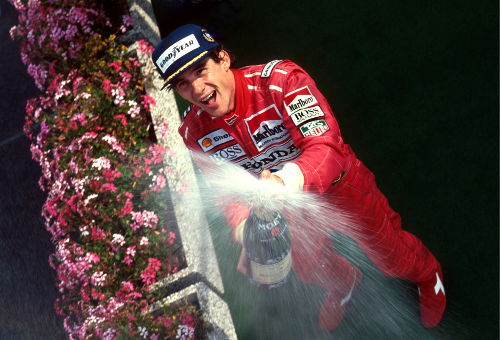Ayrton Senna sprays champagne on a Formula 1 podium